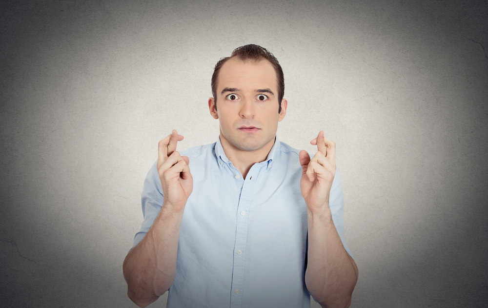 Closeup portrait young funny looking guy, sarcastic, anxious business man crossing fingers, wishing, hoping for luck, miracle isolated grey wall background. Emotions, facial expressions, feelings