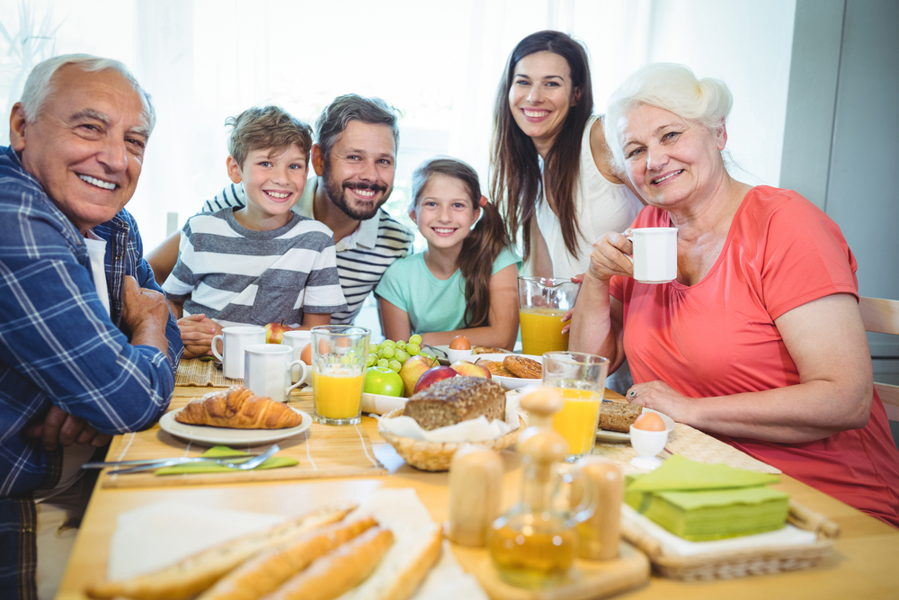 Portrait of happy multi-generation family sitting at breakfast table in home