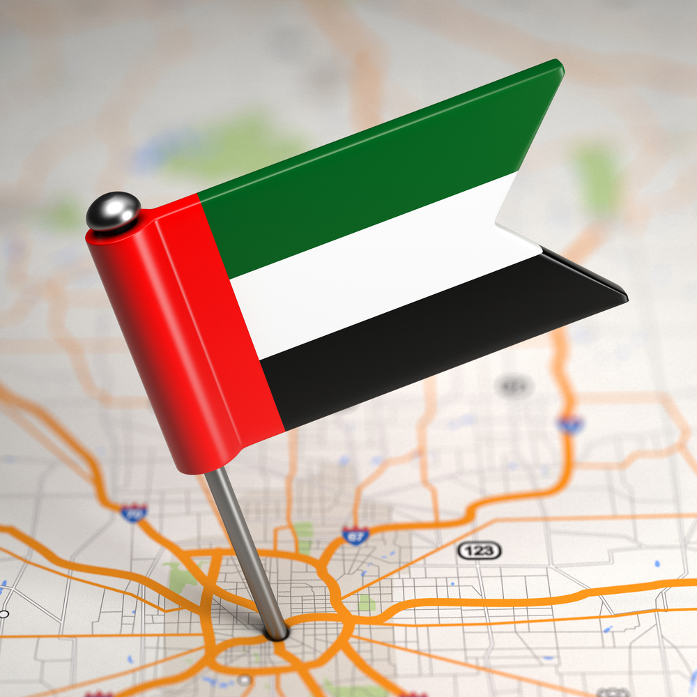 Small Flag of United Arab Emirates Sticked in the Map Background with Selective Focus.
