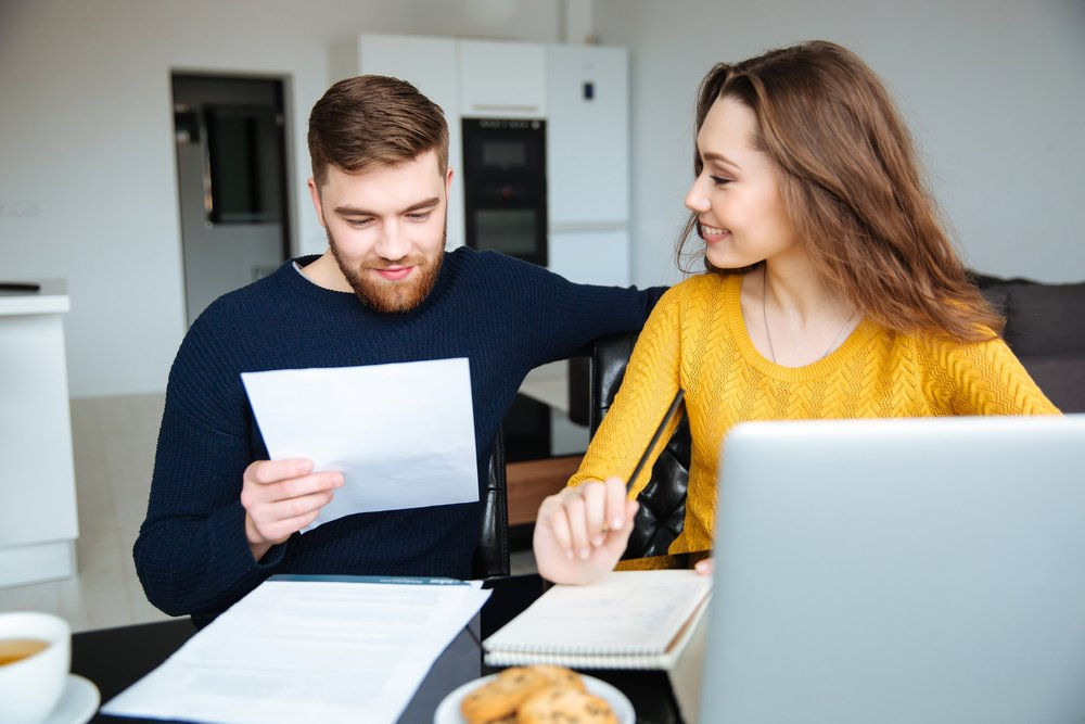 Happy young couple calculating bills at home-1