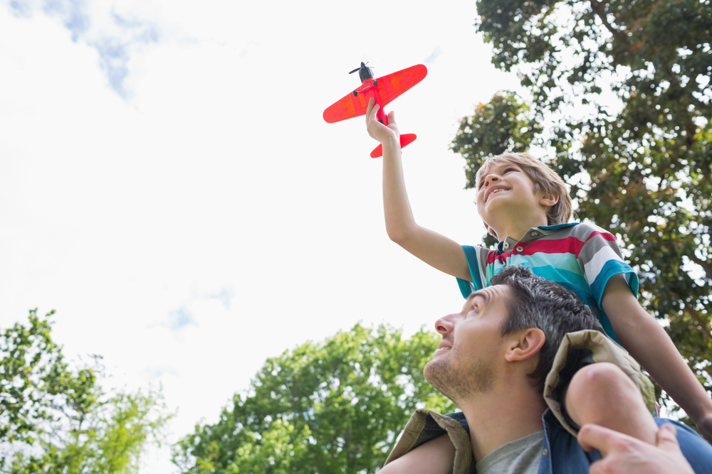 Low angle view of a boy with toy aeroplane sitting on fathers shoulders at the park-1